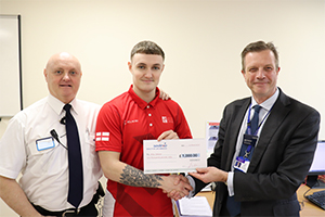 Alex Collier receives a cheque from HMP Forest Bank Director Matt Spencer alongside his father, Keith